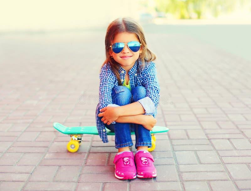 Menina de sorriso feliz do retrato à moda que senta-se no skate fotografia de stock royalty free