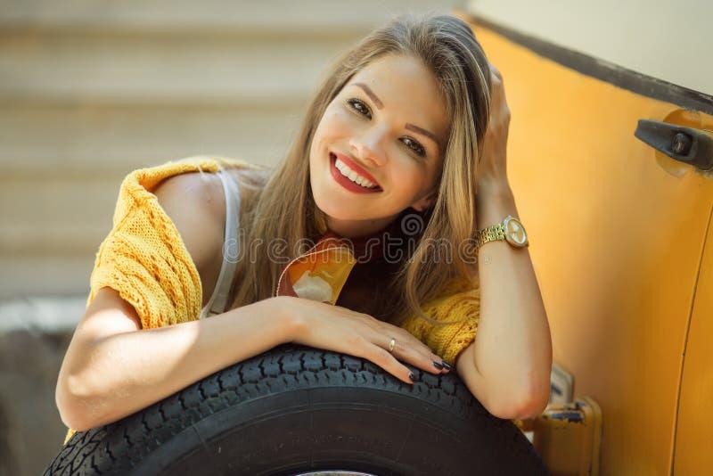 A menina de sorriso feliz está vestindo a camiseta amarela está levantando com o pneu perto do ônibus retro velho, conceito do ou imagem de stock