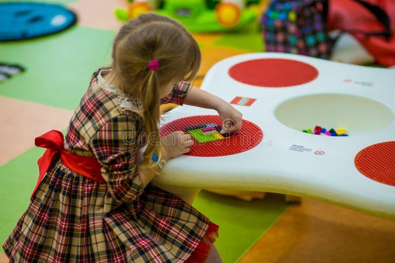 A menina de sorriso feliz joga com o construtor colorido na sala de crianças fotos de stock