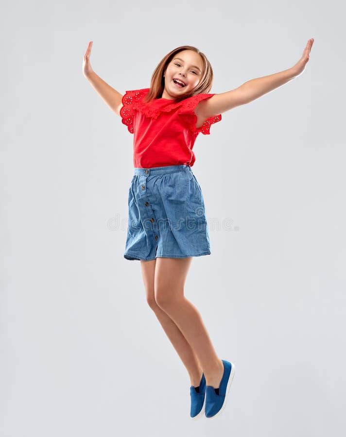 Menina de sorriso feliz no salto vermelho da camisa e da saia fotos de stock