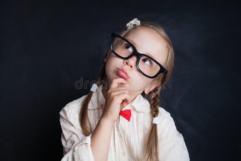 Menina de sorriso feliz nos vidros que pensa e que olha acima foto de stock royalty free