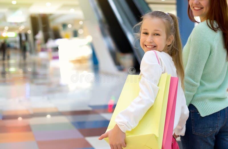 Menina de sorriso feliz que anda ao longo do shopping com seus mãe e sacos de compras imagem de stock