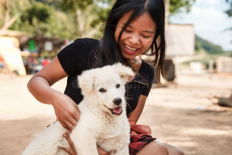 Menina de sorriso feliz que mantém um cachorrinho branco do cão em sua mão exterior fotografia de stock