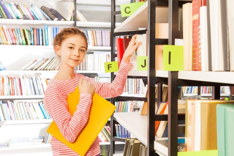 A menina de sorriso guarda o livro e está a estante próxima imagens de stock