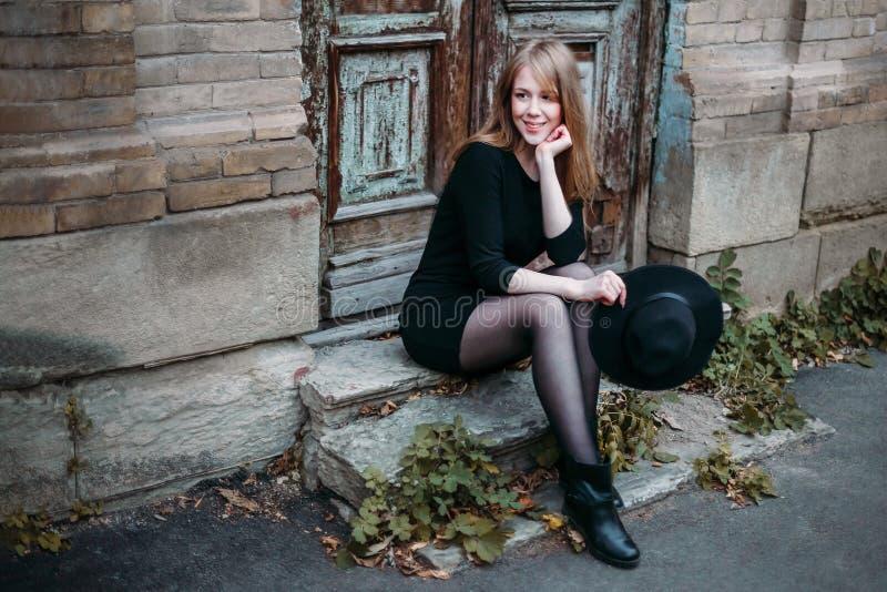 A menina de sorriso loura com cabelo longo, no vestido preto com um chapéu em suas mãos, está sentando-se nas etapas no fundo do  imagem de stock