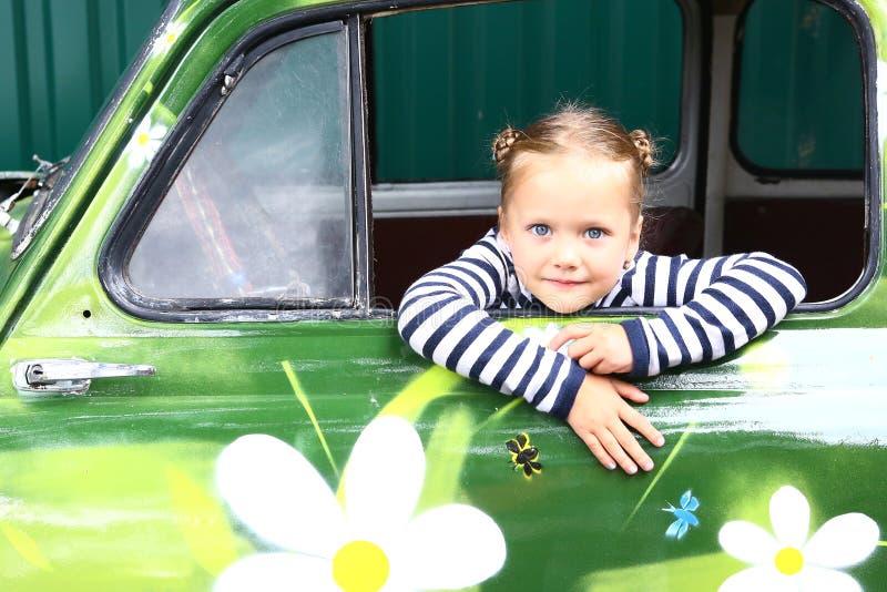 Menina de sorriso loura do preteen no carro pintado velho fotos de stock royalty free