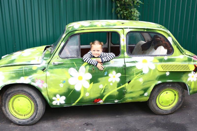 Menina de sorriso loura do preteen no carro pintado velho imagem de stock