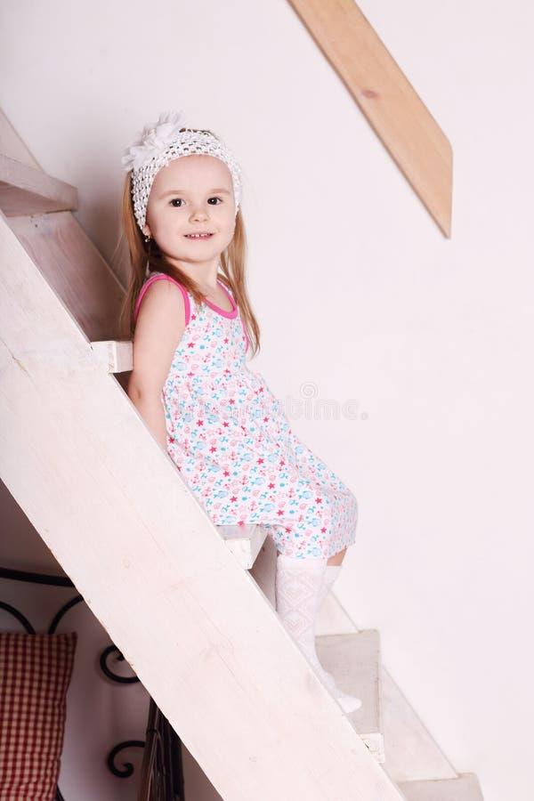 Menina de sorriso loura pequena no vestido que senta-se em escadas de madeira imagens de stock royalty free