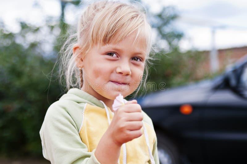 Menina de sorriso na jarda da casa rural imagem de stock