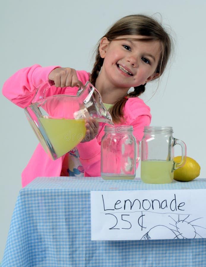 Menina de sorriso na limonada de derramamento do carrinho de limonada foto de stock royalty free