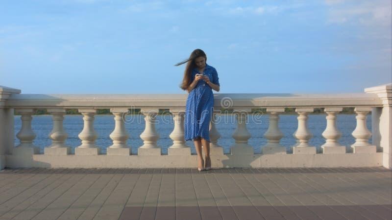Menina de sorriso na mensagem texting do vestido azul foto de stock