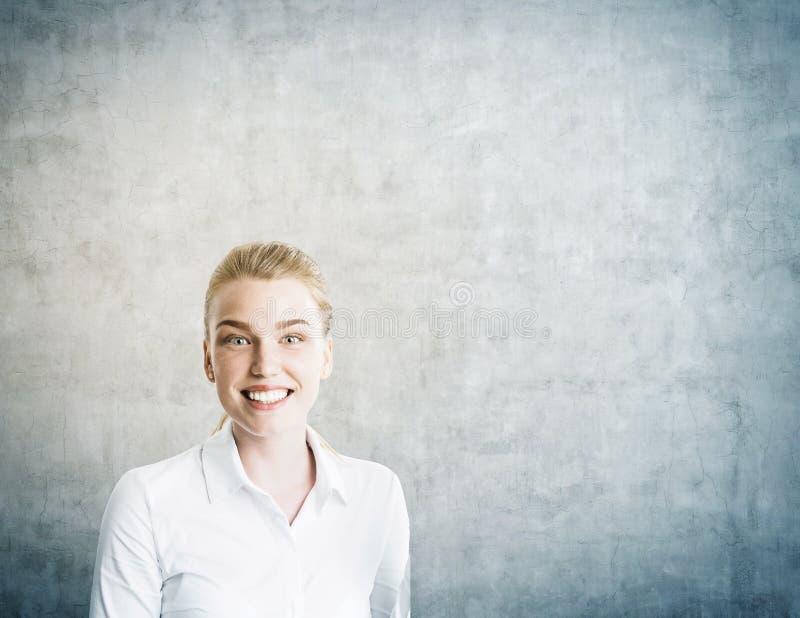 Menina de sorriso na obscuridade - sala cinzenta foto de stock royalty free