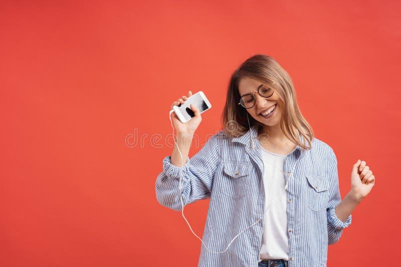 Menina de sorriso na roupa ocasional e nos fones de ouvido que dan?am as m?os moventes fotos de stock