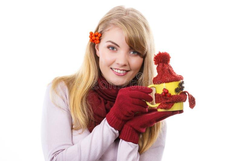 Menina de sorriso nas luvas que guardam o copo do chá com lenço e o tampão de lã fotos de stock