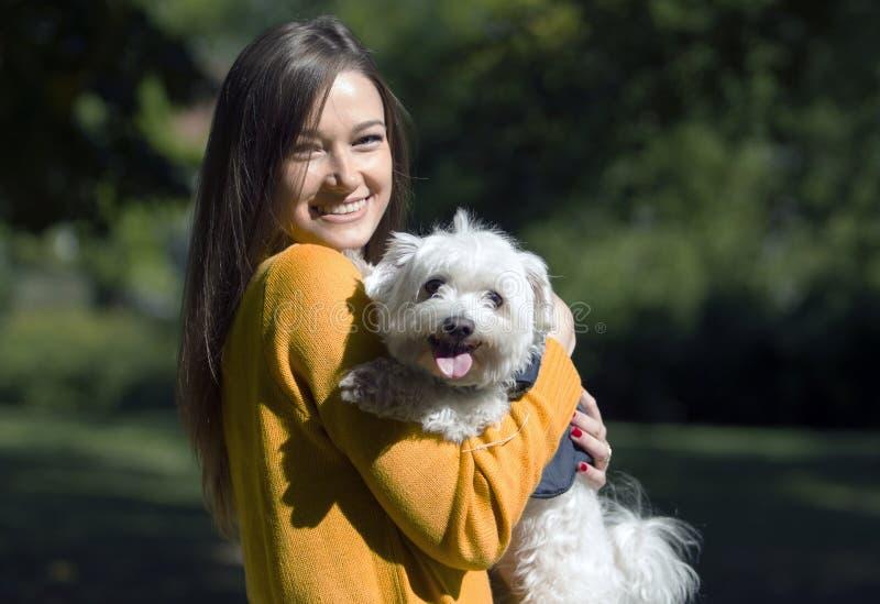 Menina de sorriso no abraço de um cão branco pequeno fotos de stock