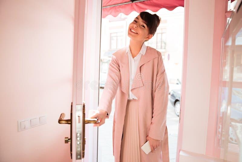 Menina de sorriso no bar entrando do revestimento cor-de-rosa imagens de stock