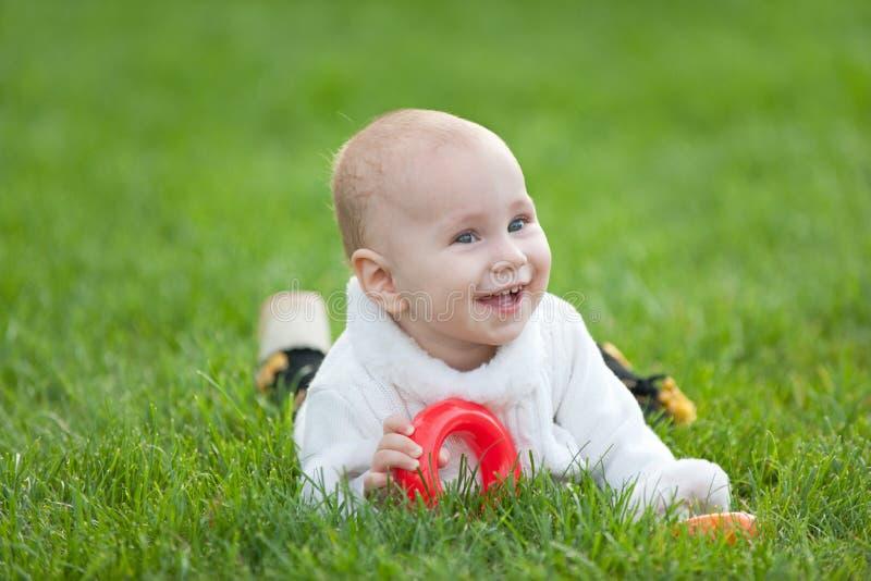 Menina de sorriso no branco na grama verde fotos de stock royalty free