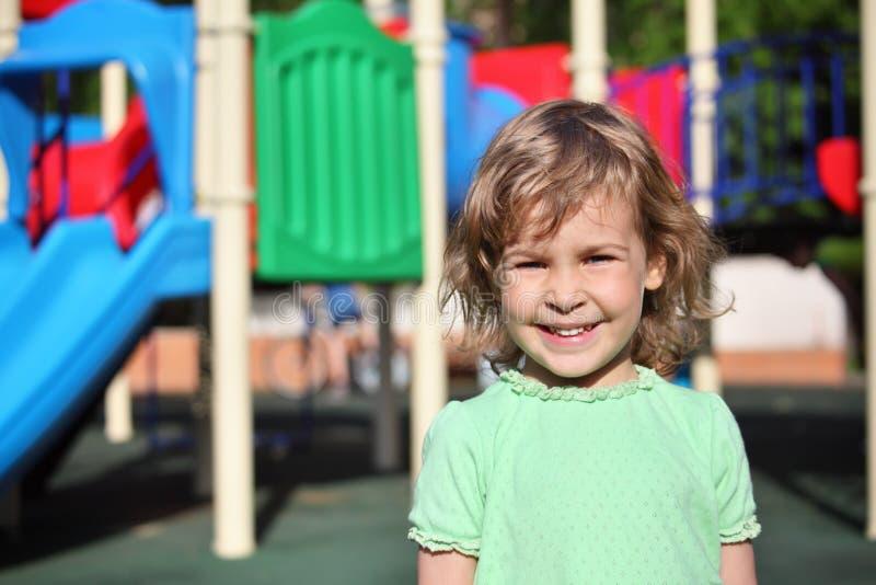 Menina de sorriso no campo de jogos foto de stock royalty free
