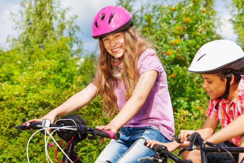 Menina de sorriso no capacete e menino africano em bicicletas imagem de stock royalty free