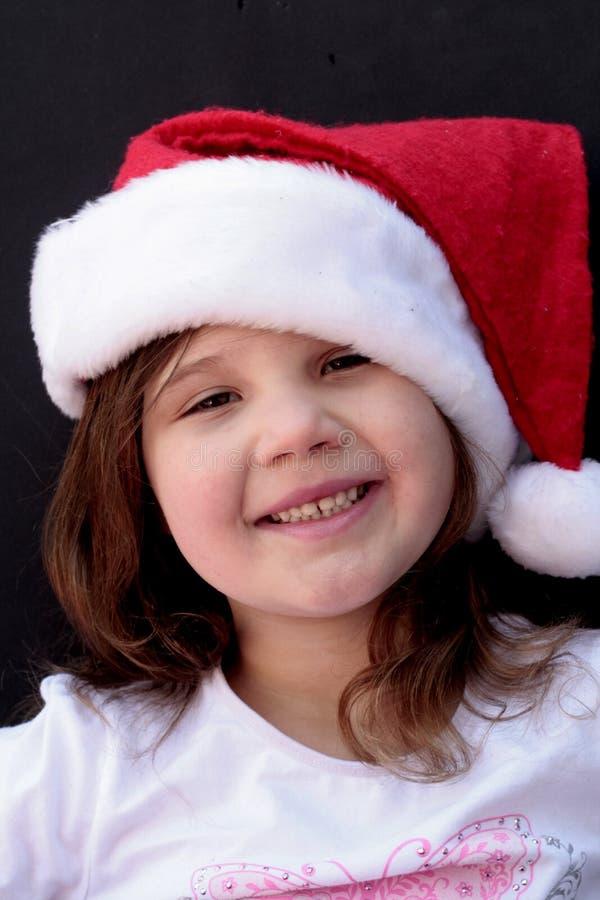 Menina de sorriso no chapéu de Santa imagens de stock royalty free