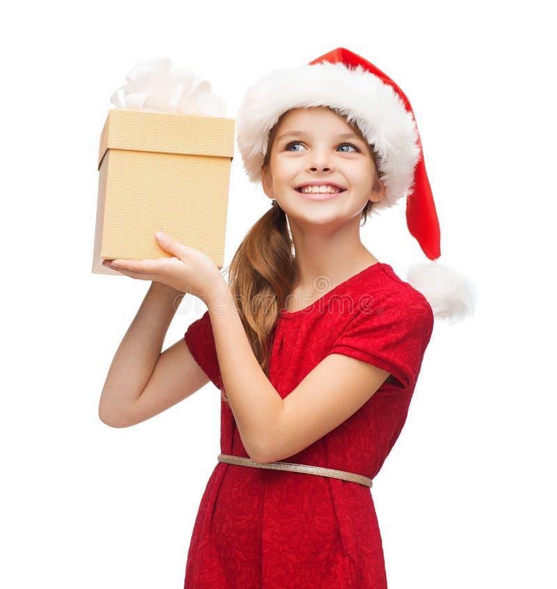 Menina de sorriso no chapéu do ajudante de Santa com caixa de presente imagens de stock