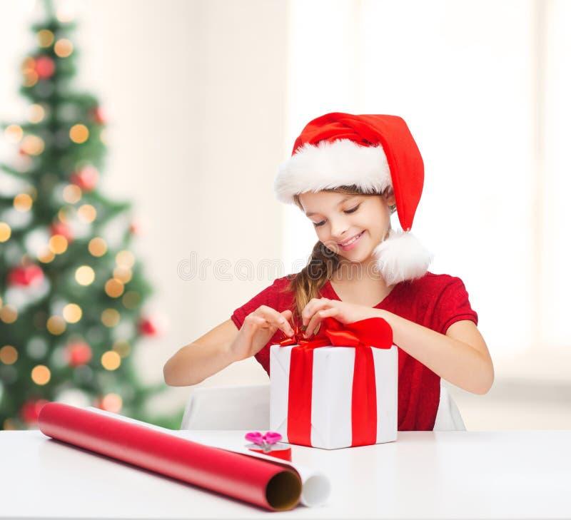 Menina de sorriso no chapéu do ajudante de Santa com caixa de presente fotos de stock royalty free