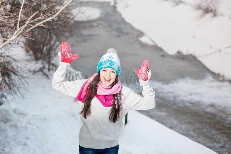 Menina de sorriso no fundo do inverno da neve foto de stock royalty free