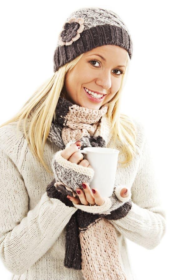 A menina de sorriso no inverno veste-se com um copo branco da bebida quente imagens de stock