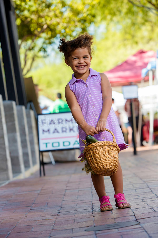Menina de sorriso no mercado dos fazendeiros fotografia de stock