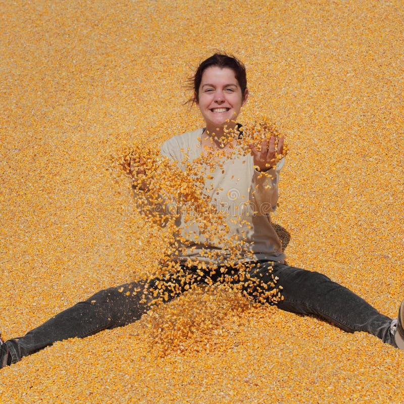 Menina de sorriso no montão do milho após a colheita imagens de stock