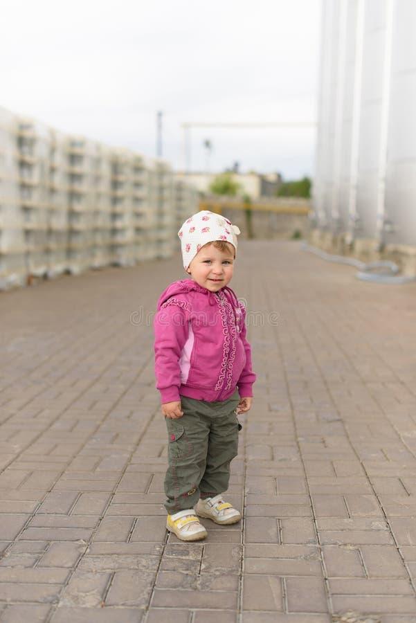 Menina de sorriso no revestimento cor-de-rosa imagem de stock