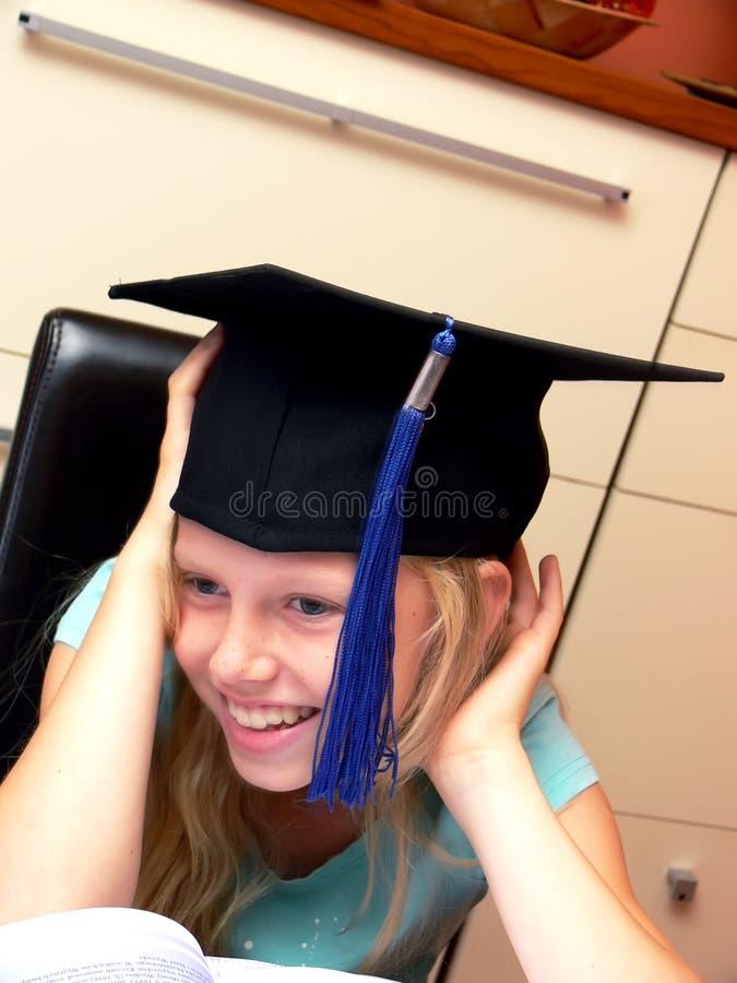 Menina de sorriso no tampão da graduação foto de stock