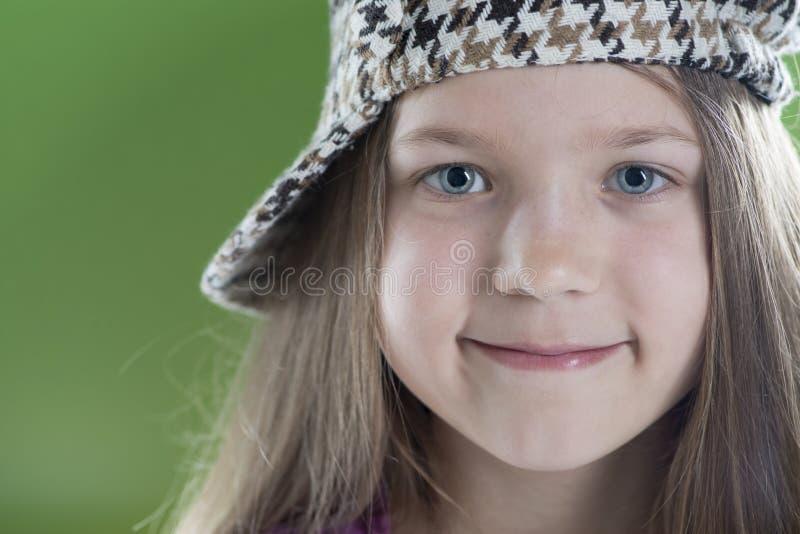 Menina de sorriso no tampão quadriculado foto de stock royalty free