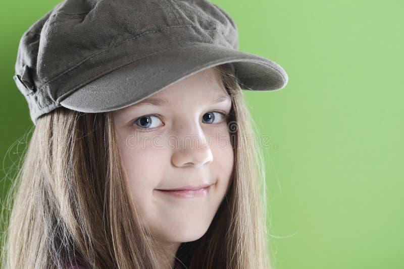 Menina de sorriso no tampão verde fotografia de stock