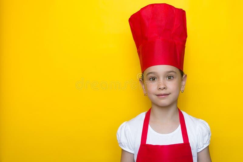 Menina de sorriso no terno vermelho do cozinheiro chefe no fundo amarelo O conceito do comida para beb? fotos de stock