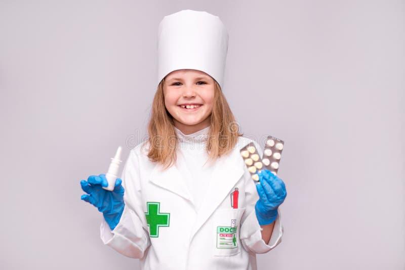 Menina de sorriso no uniforme médico que guarda o pulverizador nasal e os comprimidos para a saúde O doutor recomenda o pulveriza foto de stock
