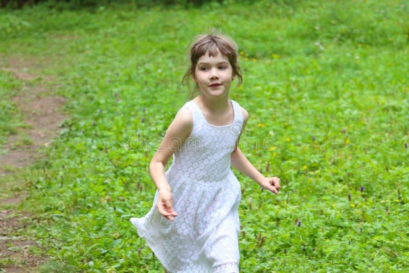 A menina de sorriso no vestido branco corre no dia de verão foto de stock