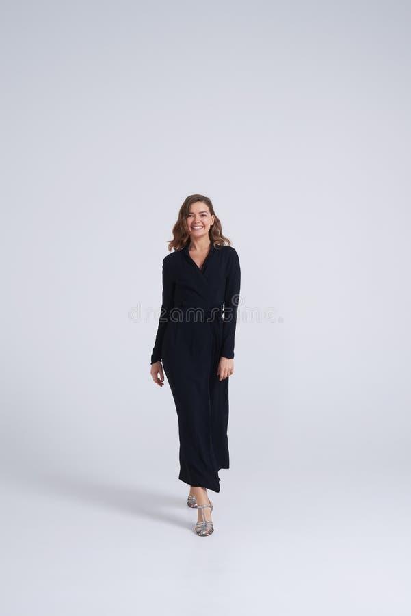 Menina de sorriso no vestido preto à moda que anda para a câmera imagem de stock royalty free