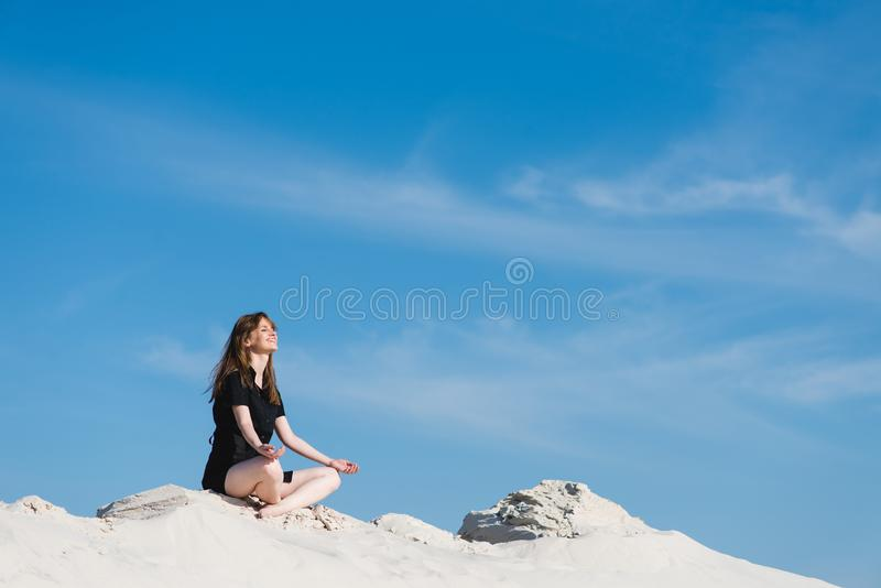 A menina de sorriso nos lótus levanta em dunas de areia imagem de stock
