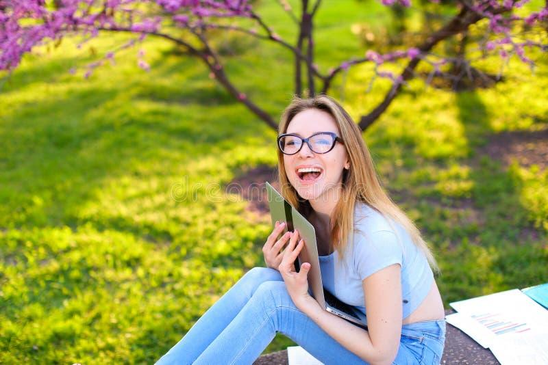 Menina de sorriso nos vidros que abraçam o portátil e que sentam-se na grama no parque fotografia de stock