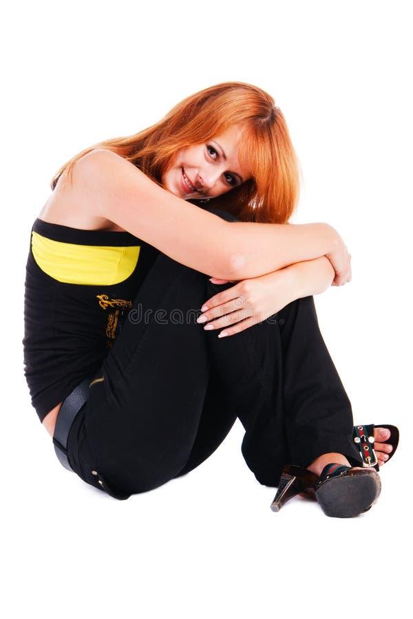 A menina de sorriso nova bonita senta-se no assoalho fotografia de stock royalty free