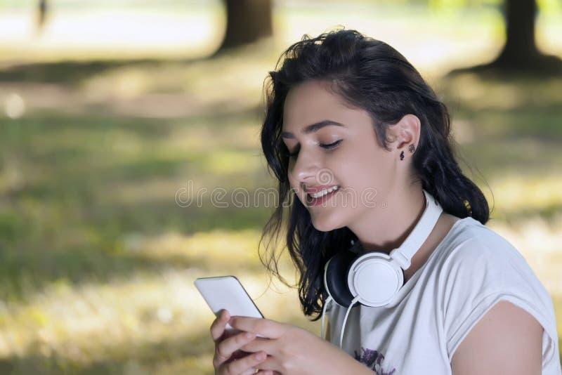 Menina de sorriso nova bonita, um adolescente, com fones de ouvido, choos imagens de stock royalty free