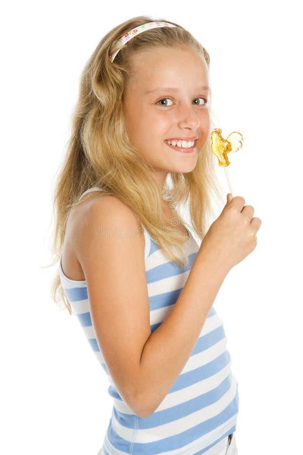 Menina de sorriso nova com doces do lollipop imagem de stock royalty free