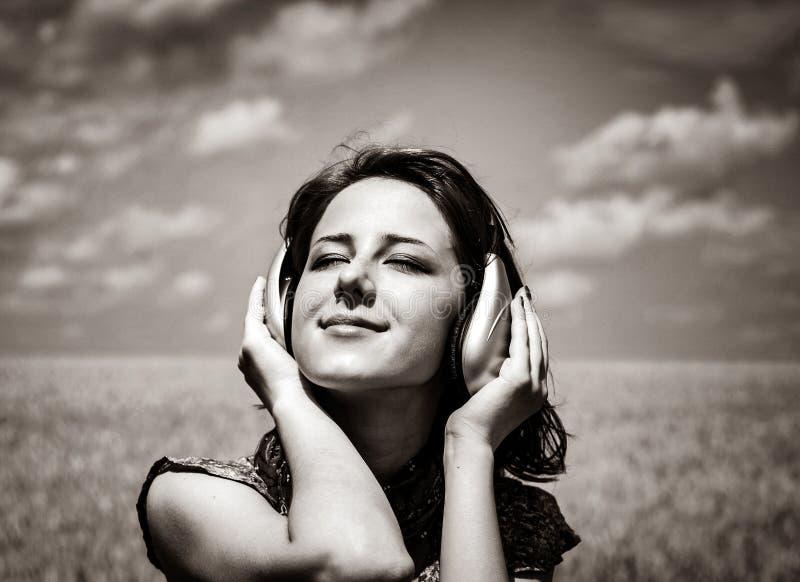 Menina de sorriso nova com os fones de ouvido no campo de trigo fotos de stock