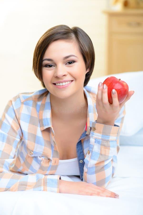 Menina de sorriso nova com uma maçã imagem de stock royalty free