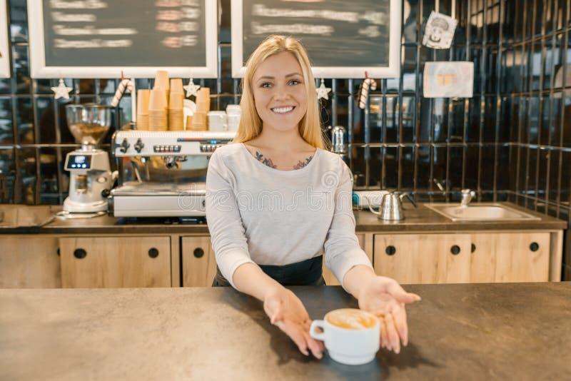 Menina de sorriso nova do barista com o copo do café recentemente preparado Mulher loura em um avental, perto do contador da barr fotografia de stock