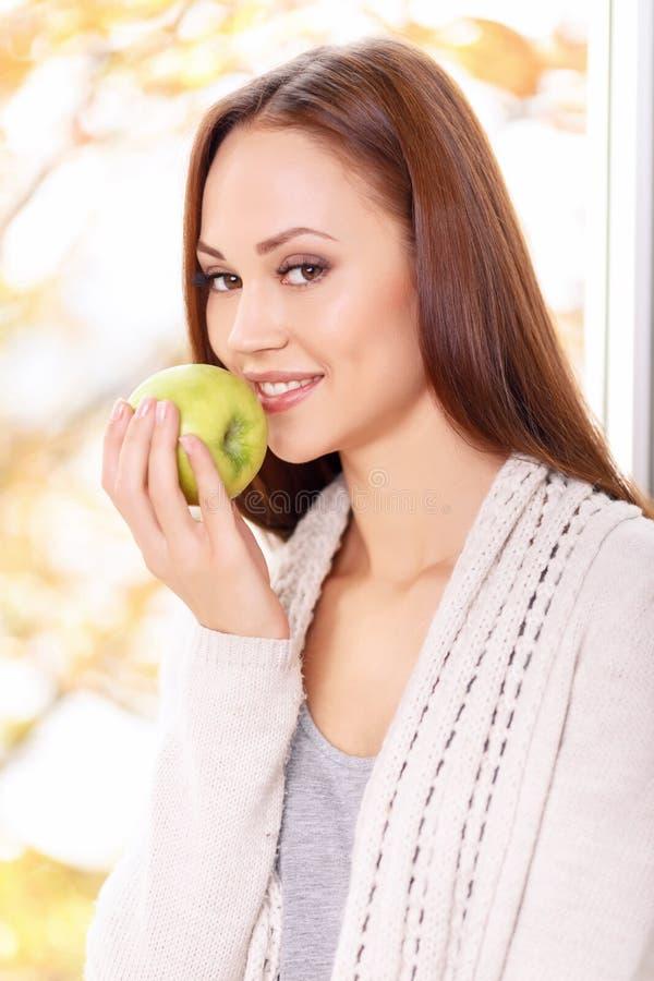 A menina de sorriso nova está a ponto de comer a maçã foto de stock