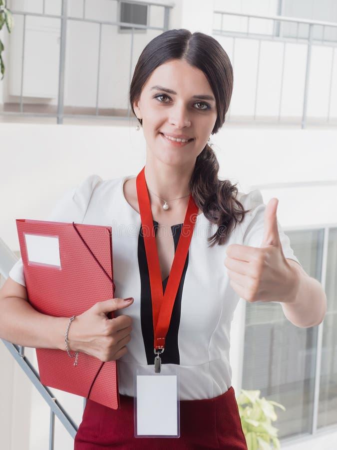 A menina de sorriso nova feita trabalho bem sucedido mostra a gesto o polegar grande acima Escritórios de sorriso bonitos de Stan fotografia de stock