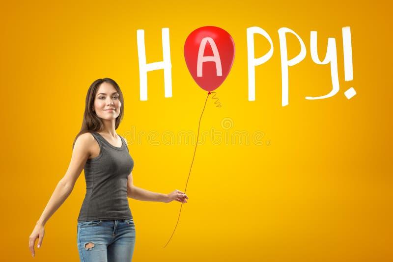 Menina de sorriso nova na roupa ocasional que está na metade-volta e que mantém o balão vermelho contra o fundo amarelo com títul imagens de stock
