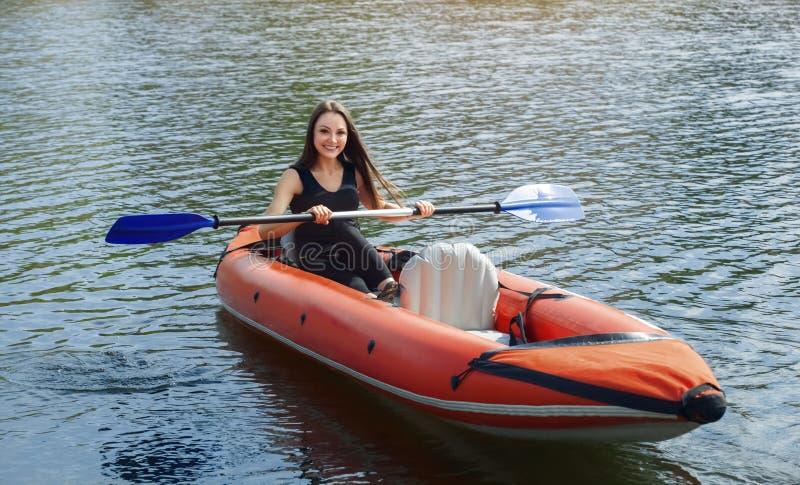 A menina de sorriso - o desportista com cabelo do longdark no blacksportswear enfileira com um remo no lago em uma canoa inflável fotos de stock royalty free